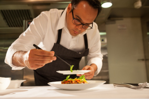 An image of a chef platting food in the kitchen - fine dining sop