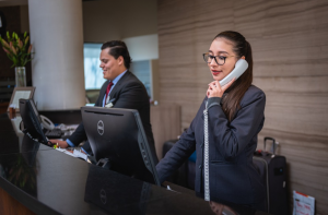 An image showing receptionists working at hotel front office department - guest arrival sop