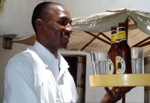 An image of a bar waiter carrying drinks on a tray